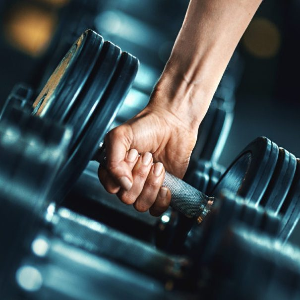Closeup side view of unrecognizable woman grabbing a dumbbell from a dumbbell rack. Shallow focus, toned image.